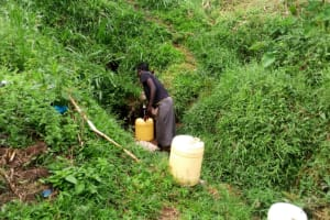 The Water Project: Ejinja Community, Anekha Spring -  Mary Fetching Water