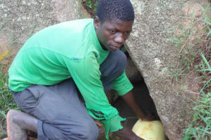 The Water Project: Chandolo Community, Joseph Ingara Spring -  Joseph Fetching Water
