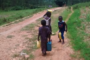 The Water Project: Ulagai Community, Rose Obare Spring -  Children Carrying Water