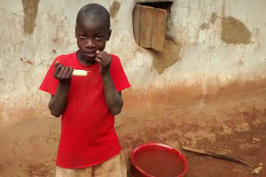 The Water Project: Elukani Community, Ongari Spring -  Child Chewing Sugarcane To Curb Hunger