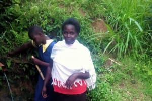 The Water Project: Mwituwa Community, Nanjira Spring -  Fetching Water