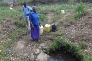 The Water Project: Ingavira Community, Laban Mwanzo Spring -  Fetching Water