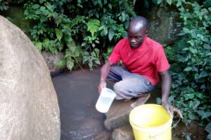 The Water Project: Muraka Community, Peter Itevete Spring -  Mr Itevete Fetching Water