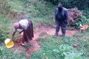 The Water Project: Koloch Community, Solomon Pendi Spring -  Mrs Pendi Fetching Water