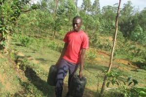 The Water Project: Essaba Secondary School -  Boy Carrying Water Back To School