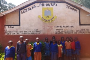 The Water Project: Shihalia Primary School -  Students Stand In Front Of School Sign