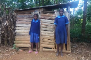 The Water Project: Shihimba Primary School -  Girls Pose In Front Of Latrines