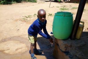 The Water Project: Emukangu Primary School, Shibuli -  Boy Washes His Hands