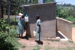 The Water Project: St. Joseph Eshirumba Primary School -  Girls Fill Watter For Latrines