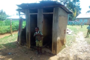The Water Project: Eshisenye Primary School -  A Boy Poses At The Boys Latrine Section