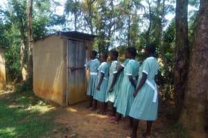 The Water Project: Eshisenye Primary School -  Girls Line Up To Use Latrine
