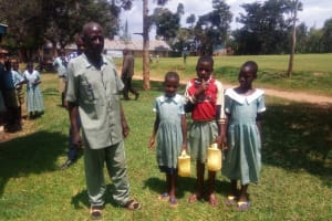 The Water Project: Eshisenye Primary School -  Schools Teacher Poses With Students At The School