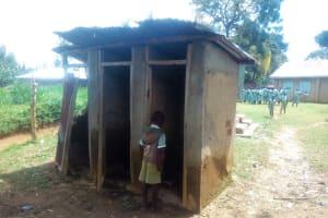 The Water Project: Eshisenye Primary School -  Student Looks Inside Broken Latrine