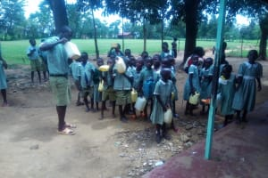 The Water Project: Eshisenye Primary School -  Students Stand With Water Collected In Containers