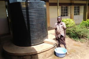 The Water Project: Shitaho Community School -  Student Stands At Rainwater Tank