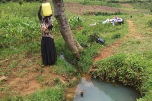 The Water Project: Matsakha Community, Siseche Spring -  Woman Hoists Jerrycan Full Of Water Onto Her Head