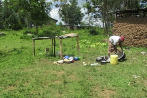 The Water Project: Luvambo Community, Timona Spring -  A Lady Washes Utensils Outside Her Home