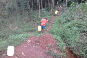The Water Project: Musutsu Community, Mwashi Spring -  Boy Carries Heavy Jerrycan Full Of Water Up Hill