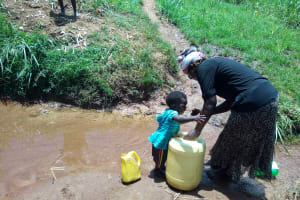 The Water Project: Chegulo Community, Yeni Spring -  Child Plays As His Mother Collects Water