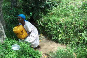 The Water Project: Muyundi Community, Ngalame Spring -  A Lady Struggles To Lift A Water Container At The Spring