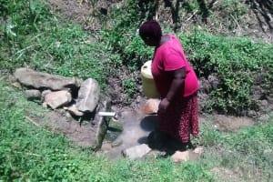 The Water Project: Ewamakhumbi Community, Yanga Spring -  A Woman Fetching Water Atbthe Spring