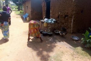 The Water Project: Isembe Community, Amwayi Spring -  A Community Member Washers Her Utensils As Ducks Eat From Them