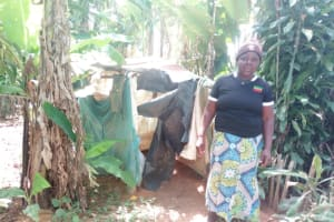 The Water Project: Isembe Community, Amwayi Spring -  Woman Stands Next To Improvised Latrine