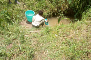 The Water Project: Emaka Community, Ateka Spring -  A Child Collects Water At The Spring