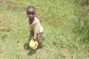 The Water Project: Emaka Community, Ateka Spring -  Child Carries Water Container