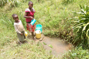 The Water Project: Emaka Community, Ateka Spring -  Children Fill Up Containers With Water