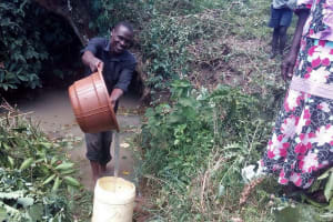 The Water Project: Lunyi Community, Fedha Mukhwana Spring -  Pouring Water Into Jerrycan