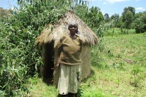 The Water Project: Shirugu Community, Jeremiah Mashele Spring -  Belinda Ogutu A Water User Stands Beside Her Grass Thatched Latrine