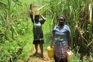 The Water Project: Shirugu Community, Jeremiah Mashele Spring -  Carrying Water Home