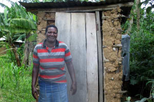 The Water Project: Shirugu Community, Shapaya Mavonga Spring -  A Community Member Stands Beside Her Latrine