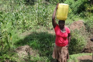 The Water Project: Ematetie Community, Weku Spring -  Carrying Jerrycan Filled With Water On Head