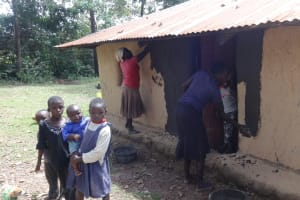 The Water Project: Ematetie Community, Weku Spring -  Community Members Smearing Their Houses For Decoration