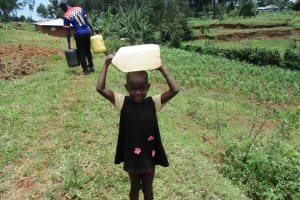 The Water Project: Chepnonochi Community, Chepnonochi Spring -  Child Carrying Water On Her Head