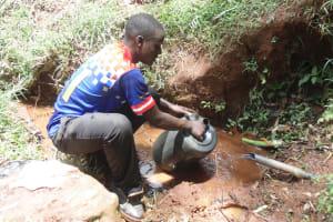 The Water Project: Chepnonochi Community, Chepnonochi Spring -  Collecting Water From Spring