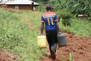 The Water Project: Chepnonochi Community, Chepnonochi Spring -  Duncun Carrying Water To His Home