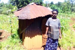 The Water Project: Upper Visiru Community, Wambosani Spring -  Mrs Obanda Beside Her Latrine