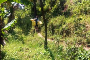 The Water Project: Emasera Community, Visenda Spring -  Child Carries Jerrycans Down To Water Source