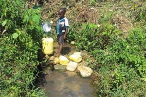 The Water Project: Emasera Community, Visenda Spring -  Child Fills Large Jerrycan