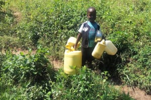 The Water Project: Emasera Community, Visenda Spring -  Childs Hands Filled With Jerrycans