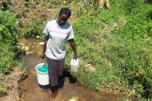 The Water Project: Emasera Community, Visenda Spring -  Woman Carries Recently Fetched Water From Spring