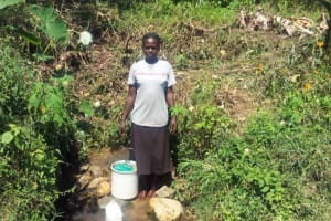 The Water Project: Emasera Community, Visenda Spring -  Woman Stands With Bucket To Collect Water