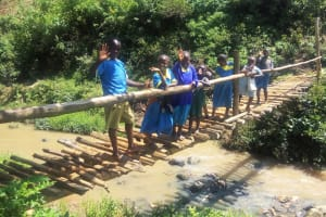 The Water Project: Emasera Community, Visenda Spring -  Young People Stand On Bridge Above Stream