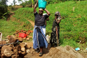 The Water Project: Ivulugulu Community, Ishangwela Spring -  Woman Carrying Materials To The Artisan
