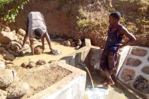 The Water Project: Musango Community, Ham Mwenje Spring -  Filling The Spring Box