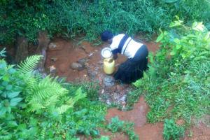 The Water Project: Shirakala Community, Ambani Spring -  Kenya Using Pot To Fill Jerrycan With Spring Water