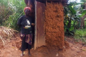 The Water Project: Emulakha Community, Alukoye Spring -  Woman Stands Next To Latrine